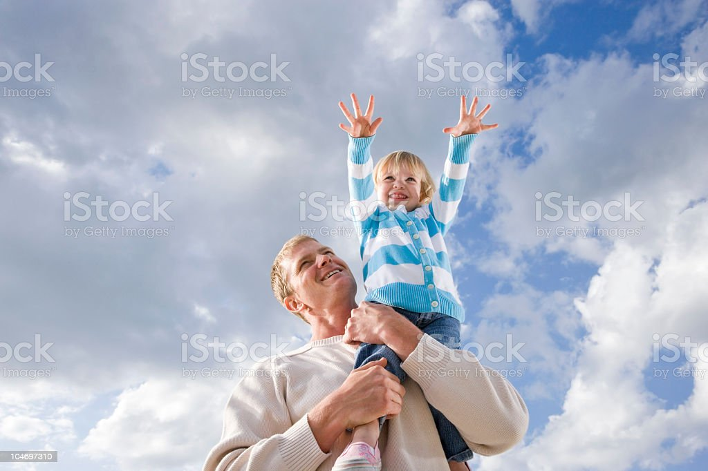 Father holding little girl high up on one shoulder royalty-free stock photo