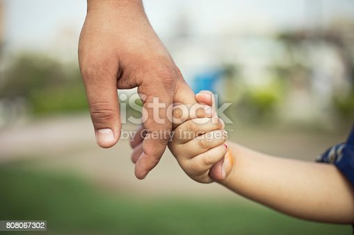 Father holding hands of his little daughter at park