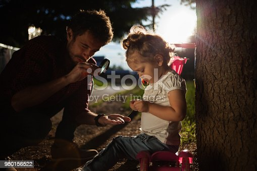 istock Father holding magnifying glass in nature with baby 980156522
