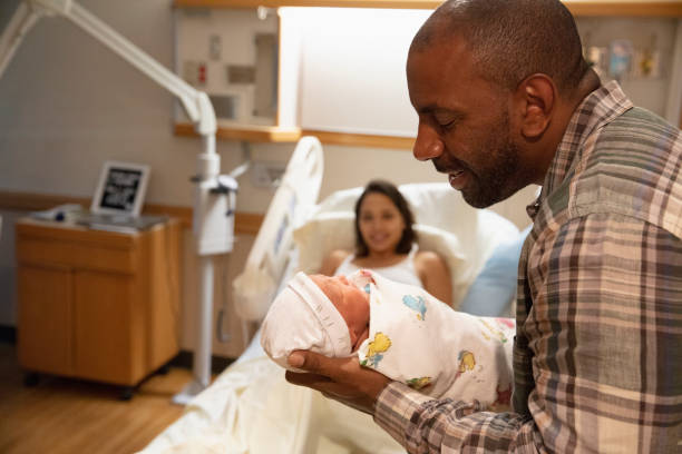 Father holding newborn baby at hospital