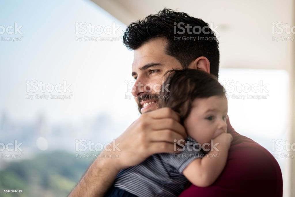 Father Holding Newborn Baby Son at Home stock photo