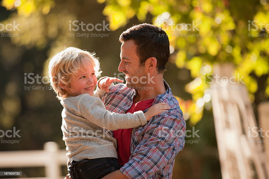 Father holding son outdoors royalty-free stock photo