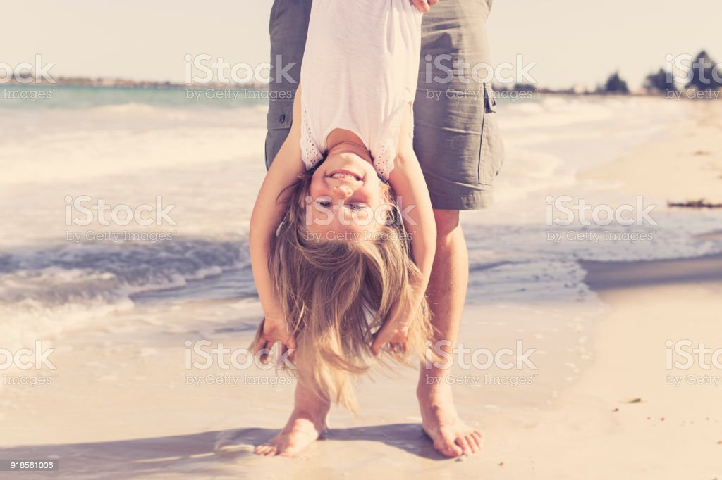 father holding sweet young and lovely blond small daughter by her feet playing having fun on the beach in dad and little girl love concept enjoying Summer holidays stock photo