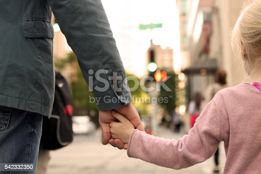 istock father holding  the daughter/ child  hand  behind  the traffic lights 542332350