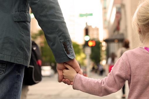 Father Holding The Daughter Child Hand Behind The Traffic Lights Foto de stock y más banco de imágenes de Acera