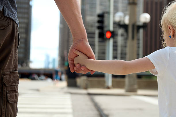 father holding  the daughter/ child  hand  behind  the traffic lights – Foto