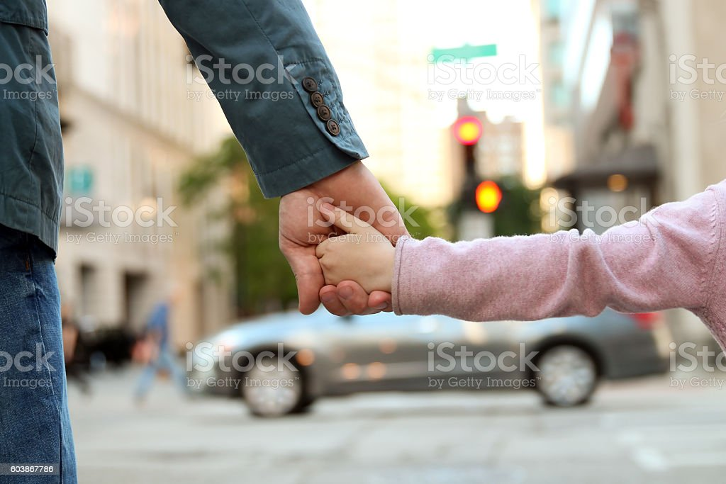 father holding  the daughter/ child  hand  behind  the traffic lights stock photo