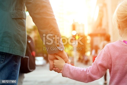 istock father holding  the daughter/ child  hand  behind  the traffic lights 837017950