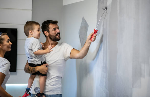 Father holds child in one hand and with the other hand paints walls in new apartment, renovates apartment for moving in stock photo