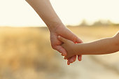 Father holds daughter by the hand