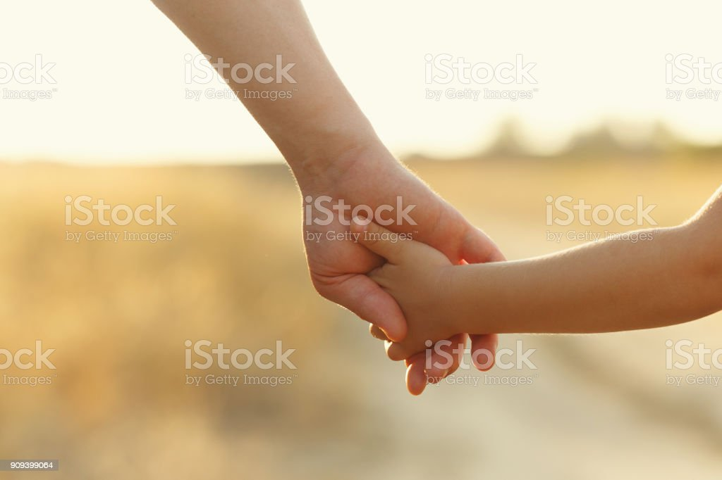 Father holds daughter by the hand stock photo