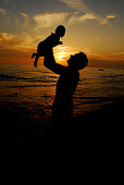 Father holds his baby up in the air on a beach by sunset