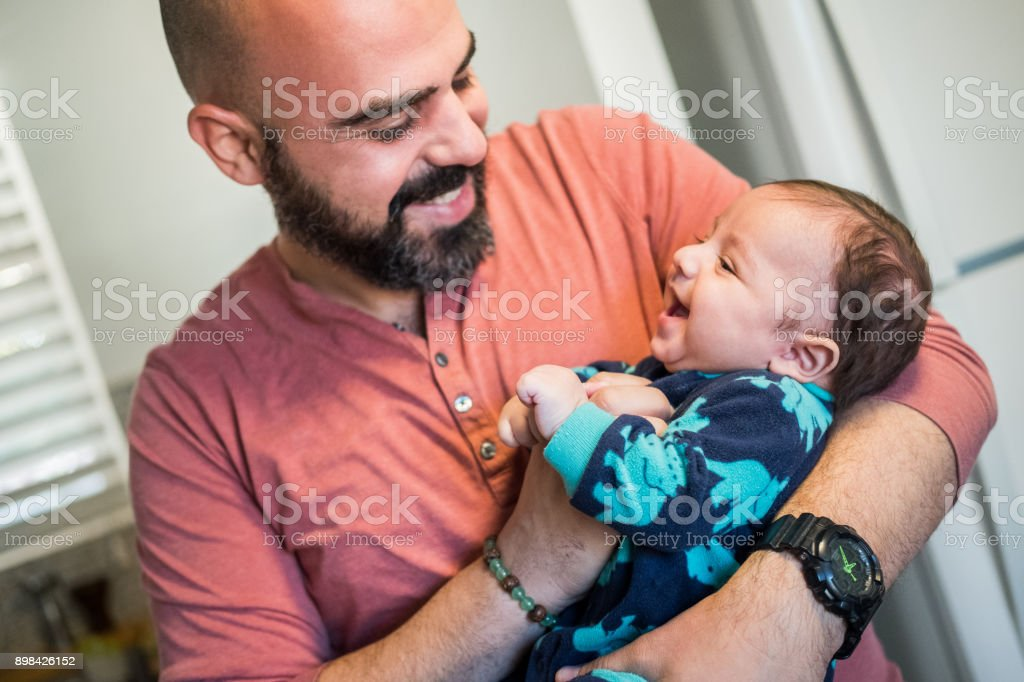 Father holds infant son stock photo