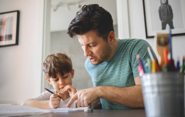 Father homeschooling his son stock photo