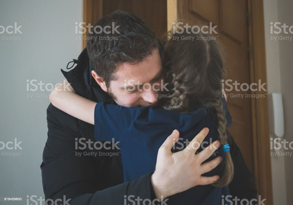 Father hugging her daughter after long trip. stock photo