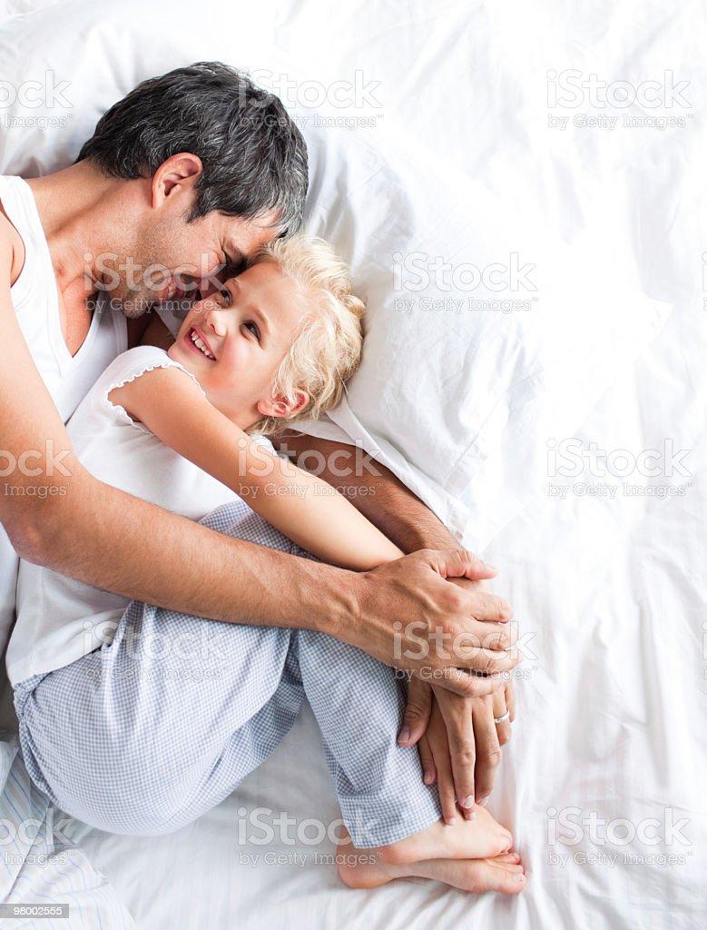 Pai e sua filha, abraçando na cama foto royalty-free
