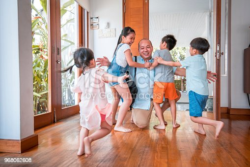 670900812istockphoto Father hugging his children when coming home 968062608