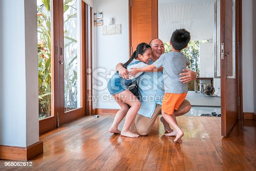 670900812istockphoto Father hugging his children when coming home 968062612