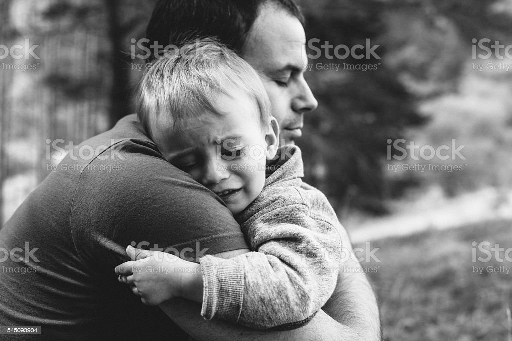 Father hugging his crying son stock photo
