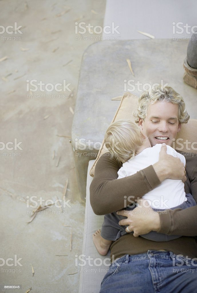 Father hugging son on patio bench royalty-free stock photo