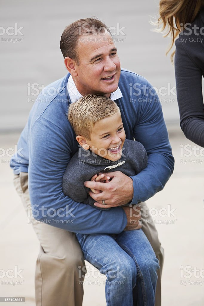 Father hugging son outdoors stock photo