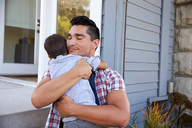 Father Hugging Son Sitting On Steps Outside Home Father Hugging Son Sitting On Steps Outside Home latin american and hispanic ethnicity stock pictures, royalty-free photos & images
