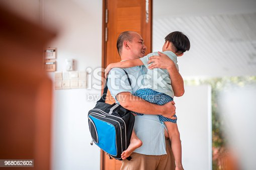 670900812istockphoto Father hugging son when coming home 968062602