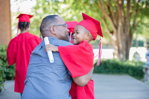 Father hugs his young son after preschool graduation ceremony