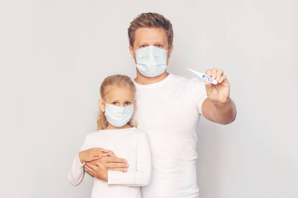 Father in a medical mask measures his daughter's temperature with an electronic thermometer on an isolated background stock photo