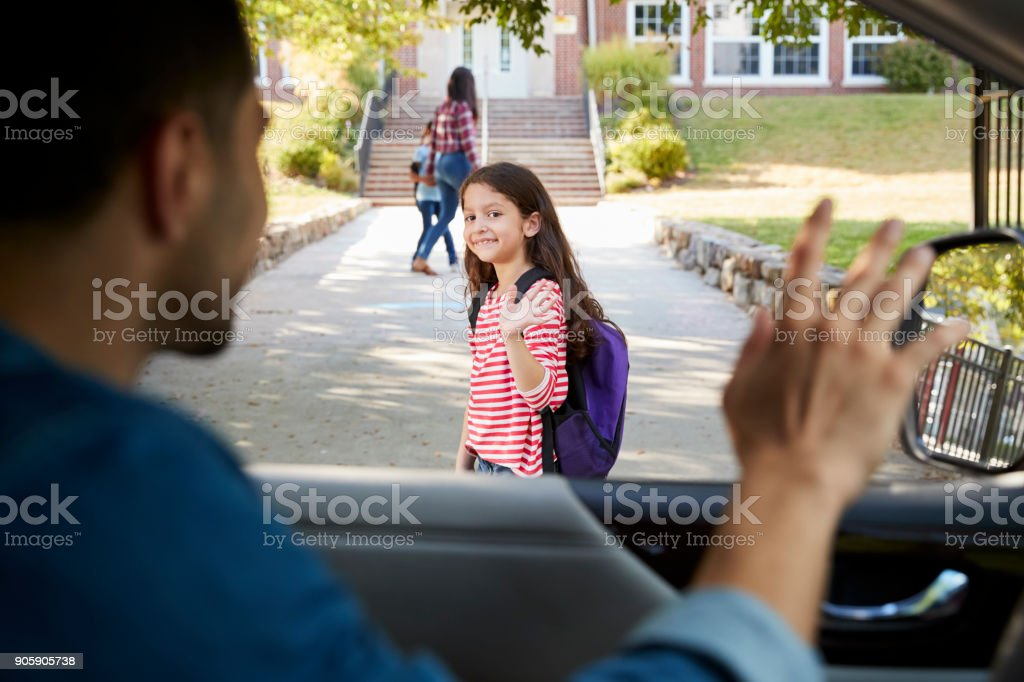 Father In Car Dropping Off Daughter In Front Of School Gates stock photo