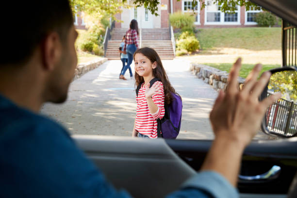 father in car dropping off daughter in front of school gates - school building stock photos and pictures