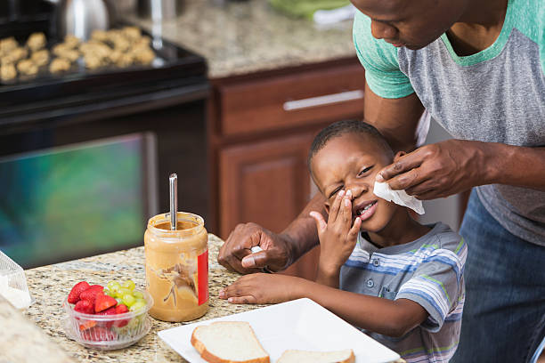 father in kitchen taking care of little boy, wiping nose - food allergies stock photos and pictures