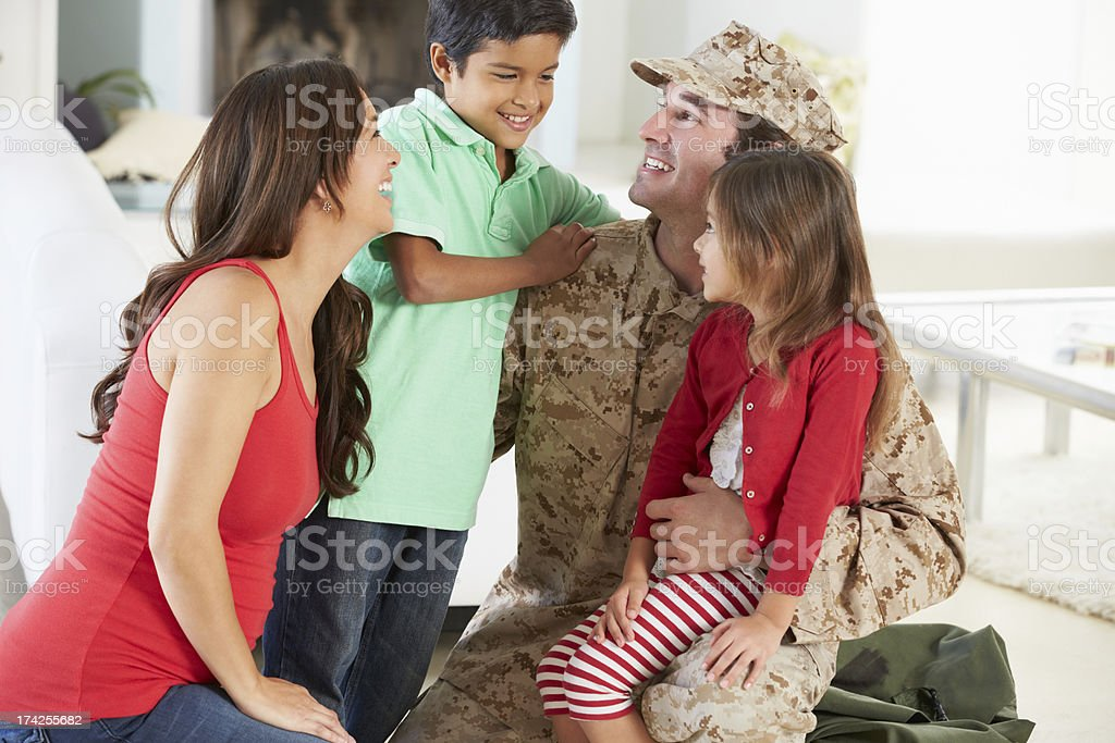 Father in military fatigues greets his wife and two children stock photo