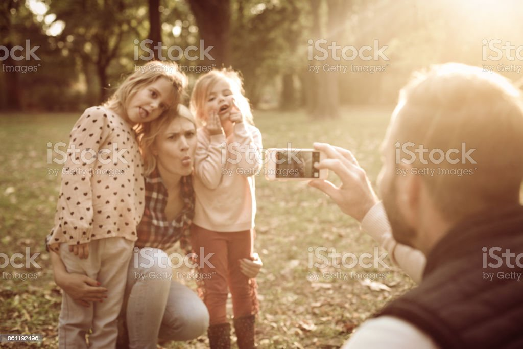 Father in park taking self portrait of his family. royalty-free stock photo