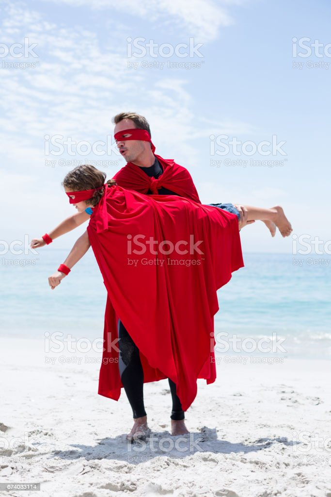 Father in superhero costume lifting son at sea shore royalty-free stock photo