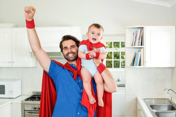 father in superhero costume lifting son in kitchen - baby super hero imagens e fotografias de stock