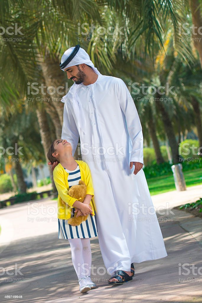 Father in traditional dress with his young daughter in park. stock photo