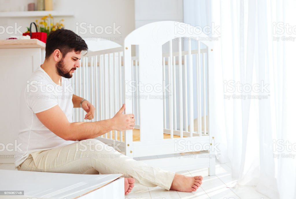 father installing the crib, preparing for a new baby in the family stock photo