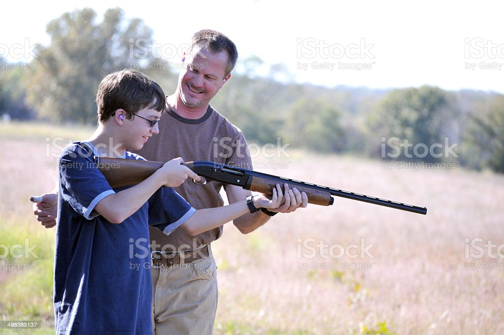 Father Instructing his Son on Proper Gun Safety stock photo