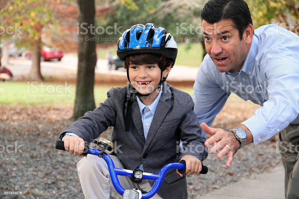 Father is helping his son keeping his balance in park stock photo