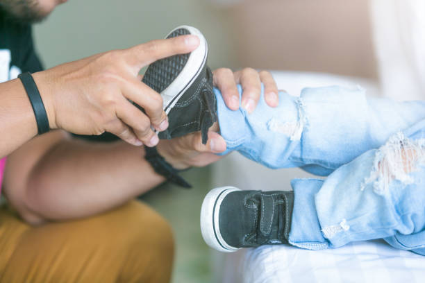 Father is helping his son to tie his shoes in the room on bed. stock photo