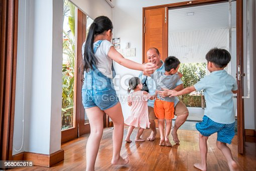 670900812istockphoto Father hugging his children when coming home 968062618