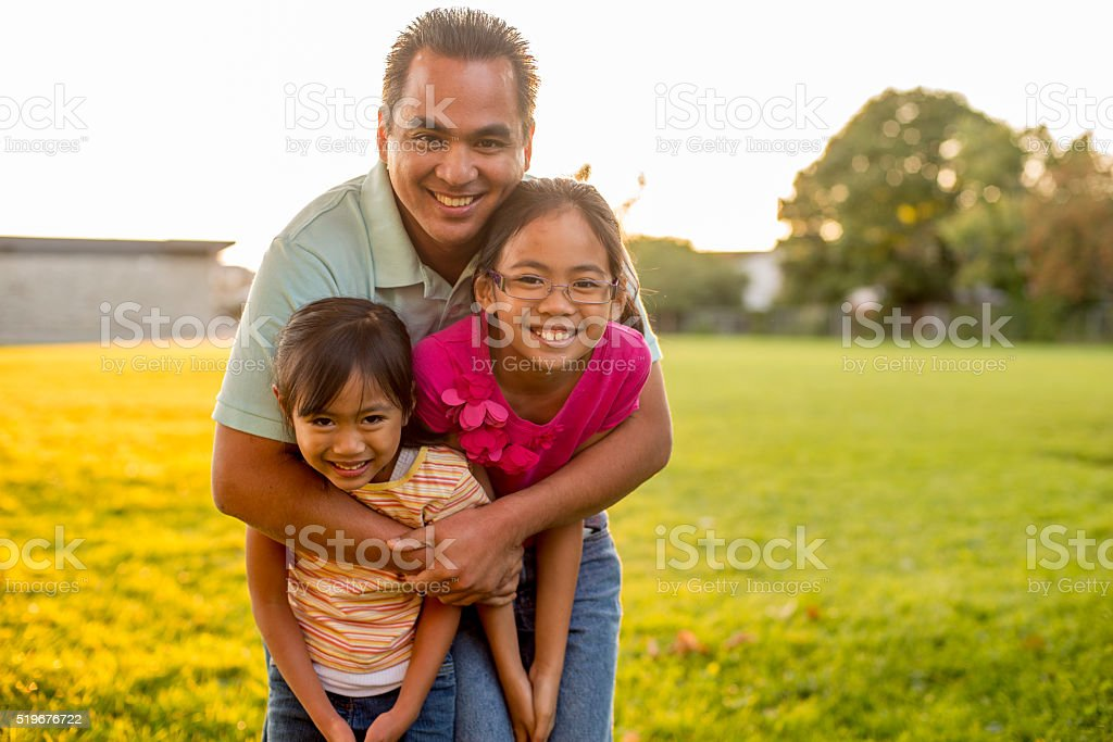 A father is standing with his daughters and is giving stock photo