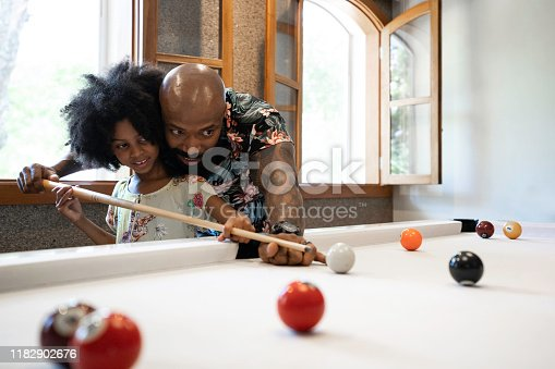 Father is teaching daughter how to play snooker