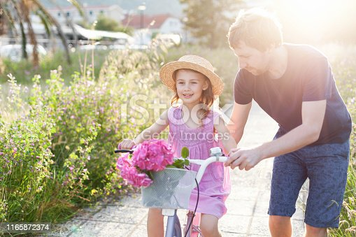 istock Father is teaching daughter to ride on bicycle. Family summer activities. Happy kid girl has support from daddy. Child smiles and has fun. 1165872374