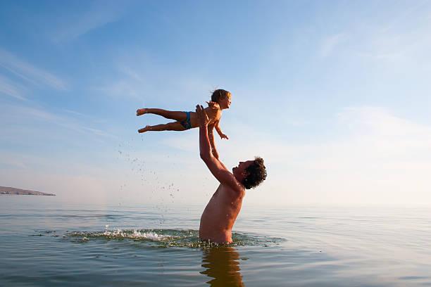 padre es tossing un hijo en agua - intergénero fotografías e imágenes de stock