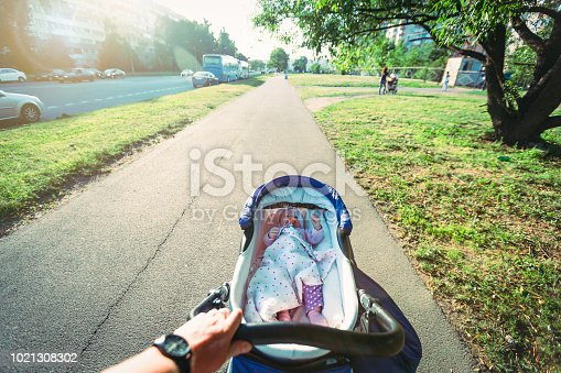 Father is walking with his baby on the street in town.Cute baby baby girl pacifier lies in baby carriage