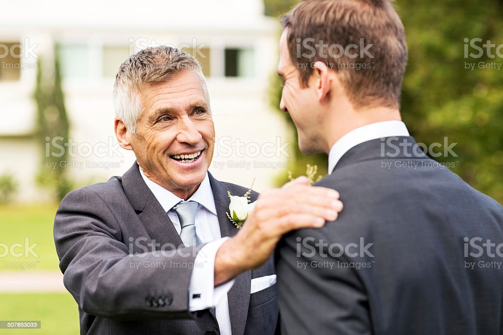 Father Keeping His Hand On Groom's Shoulder In Garden royalty-free stock photo