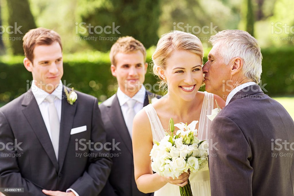 Father Kissing Bride On Cheek During Outdoor Wedding stock photo