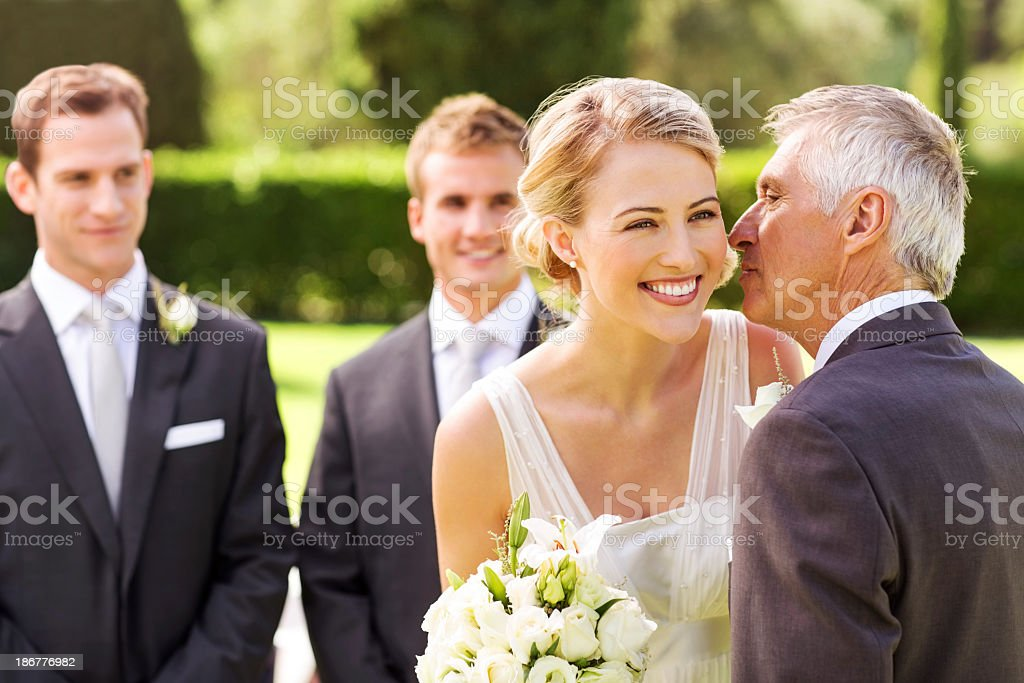 Father Kissing Bride On Cheek During Wedding Ceremony stock photo